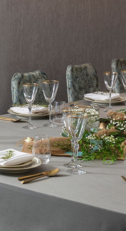 A closeup of a table lined with gold-rimmed glasses and cutlery.